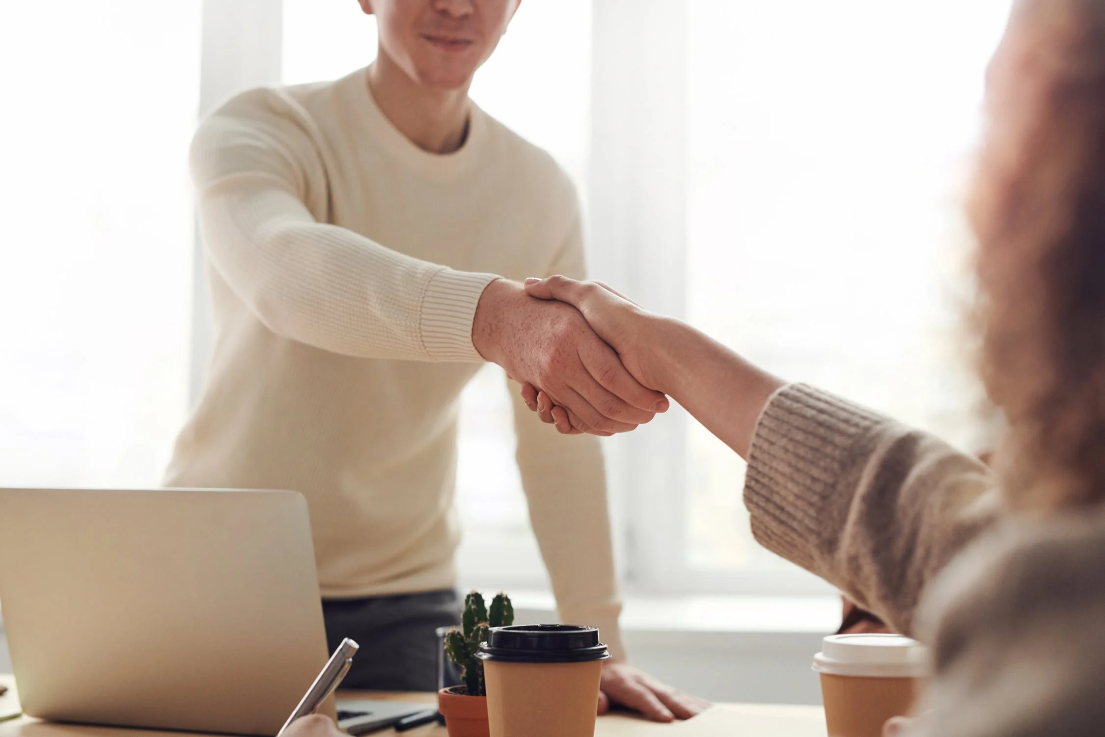 Man shaking hands with female interviewer during a job interview.