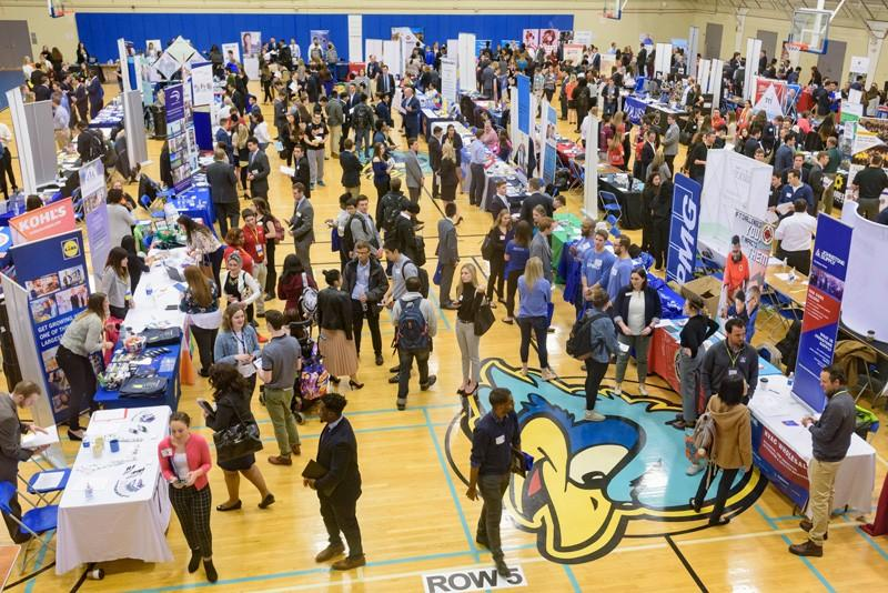 This is an example of what a college career fair looks like. It is in a gymnasium, packed with employers who want to showcase their companies, and students who want to apply for work.