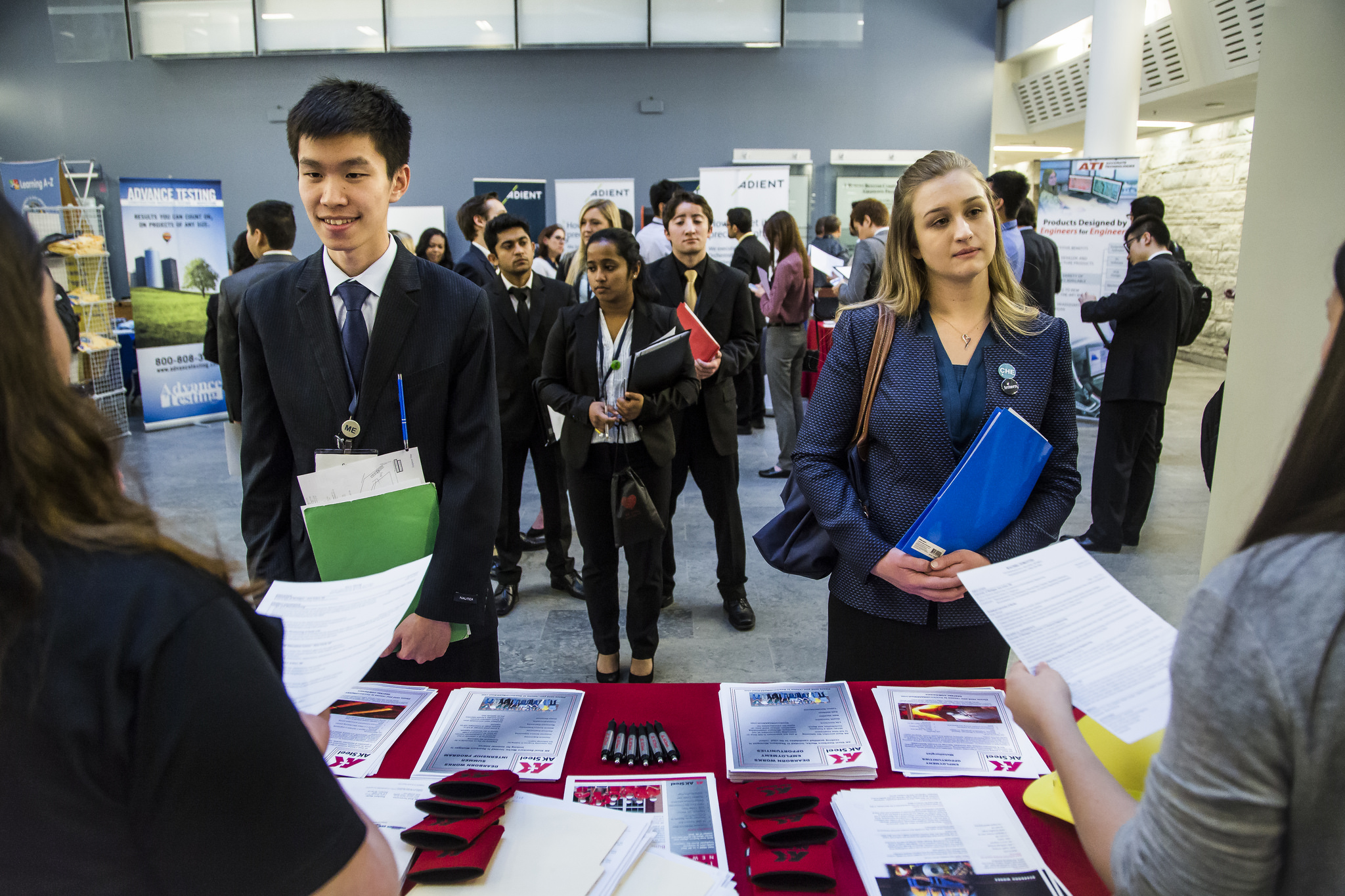 This is a picture of two students talking to employers and being handed information about their company.