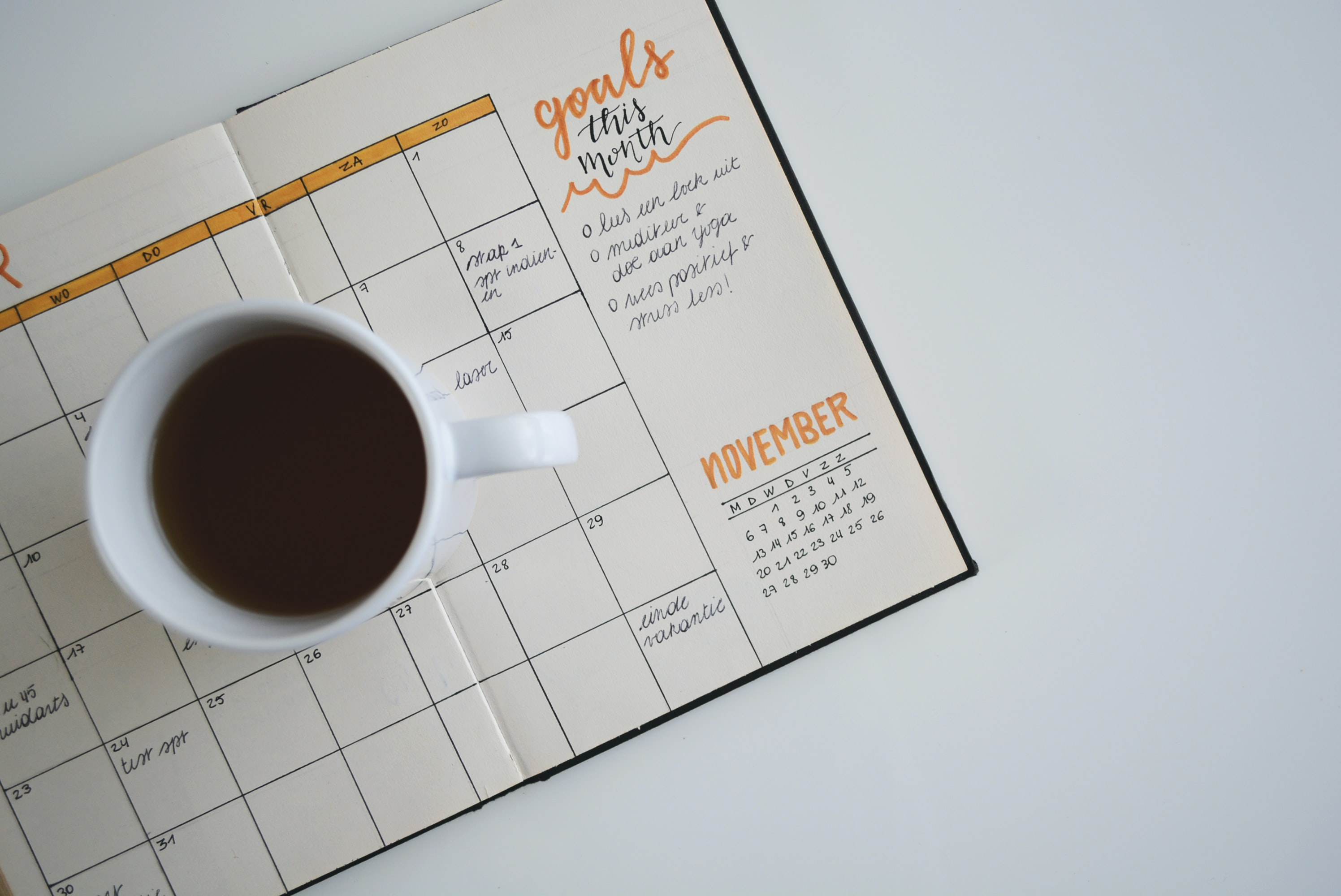 A cup of coffee set on a bullet journal.