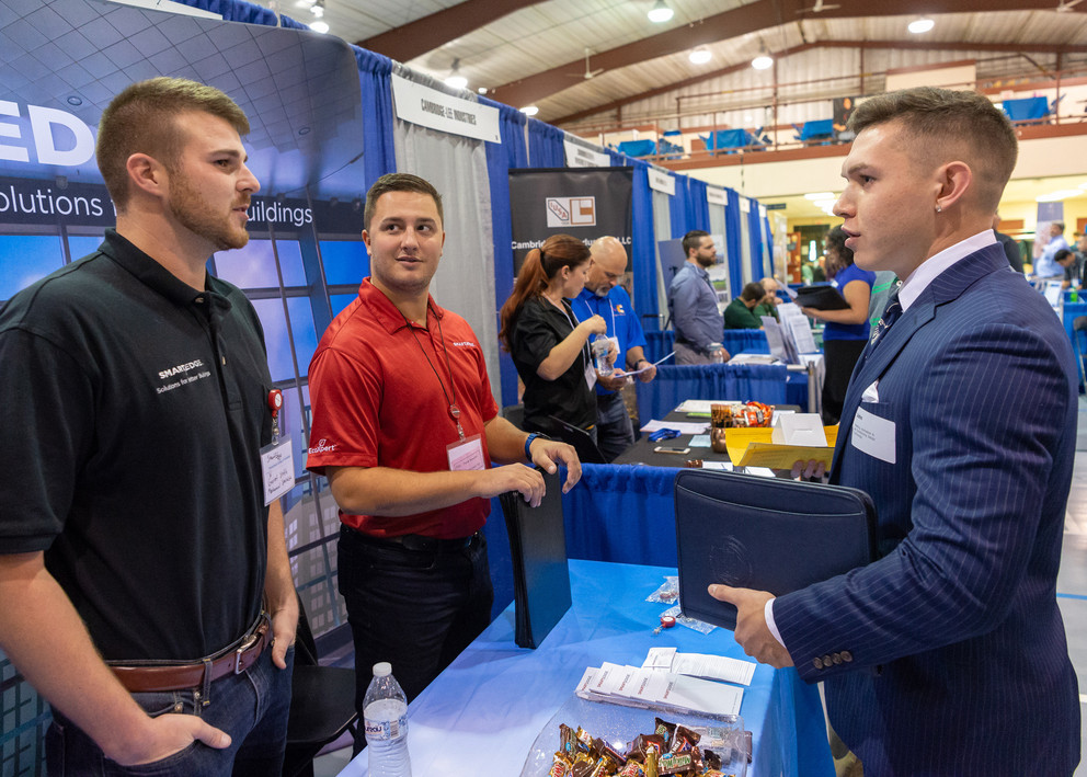 This is a picture of a student approaching a company's booth in order to talk to them about what they do.
