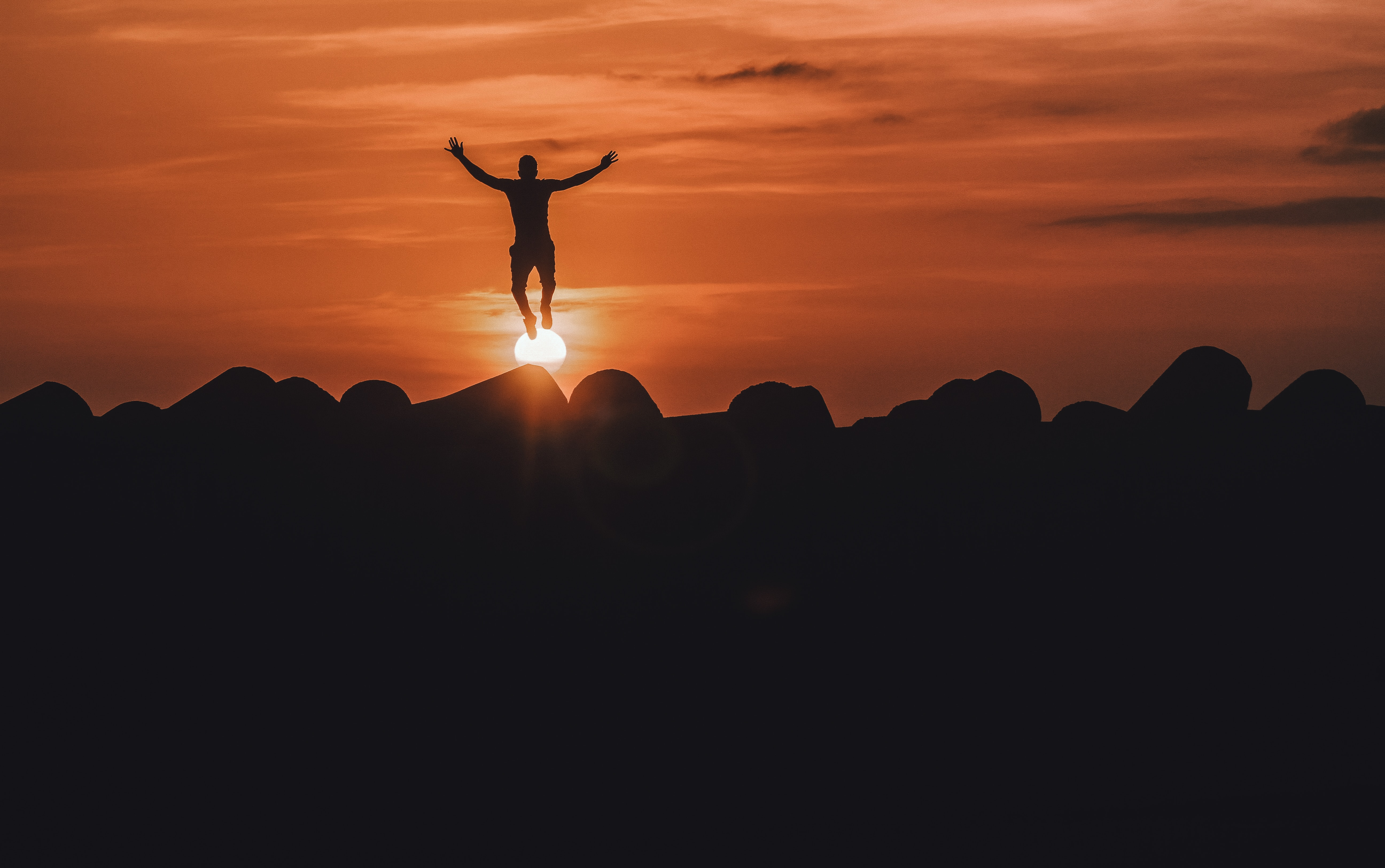 A man jumping with joy in the sunset.