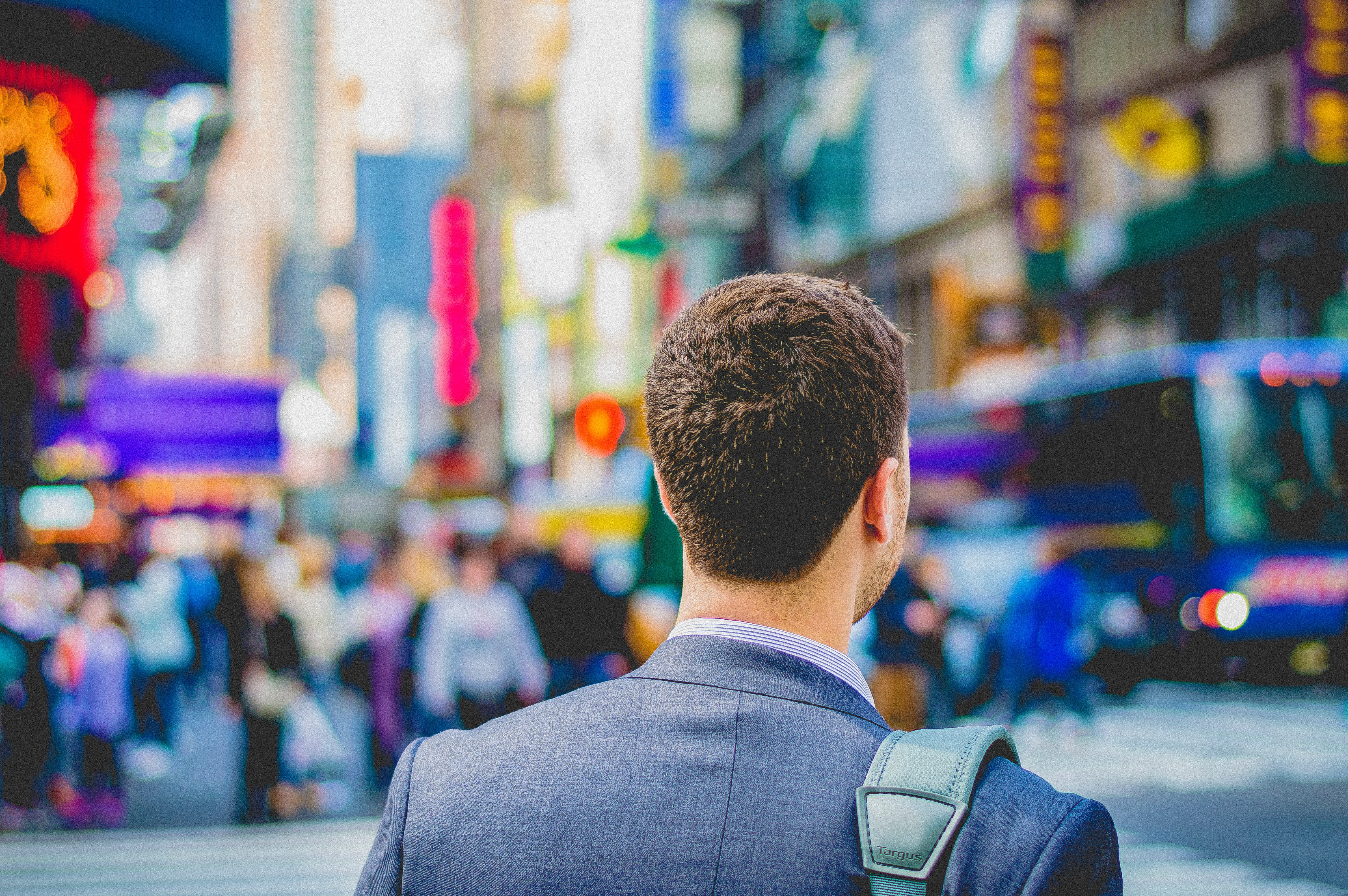 The back of a man in a suit jacket standing in the middle of a bustling city street.