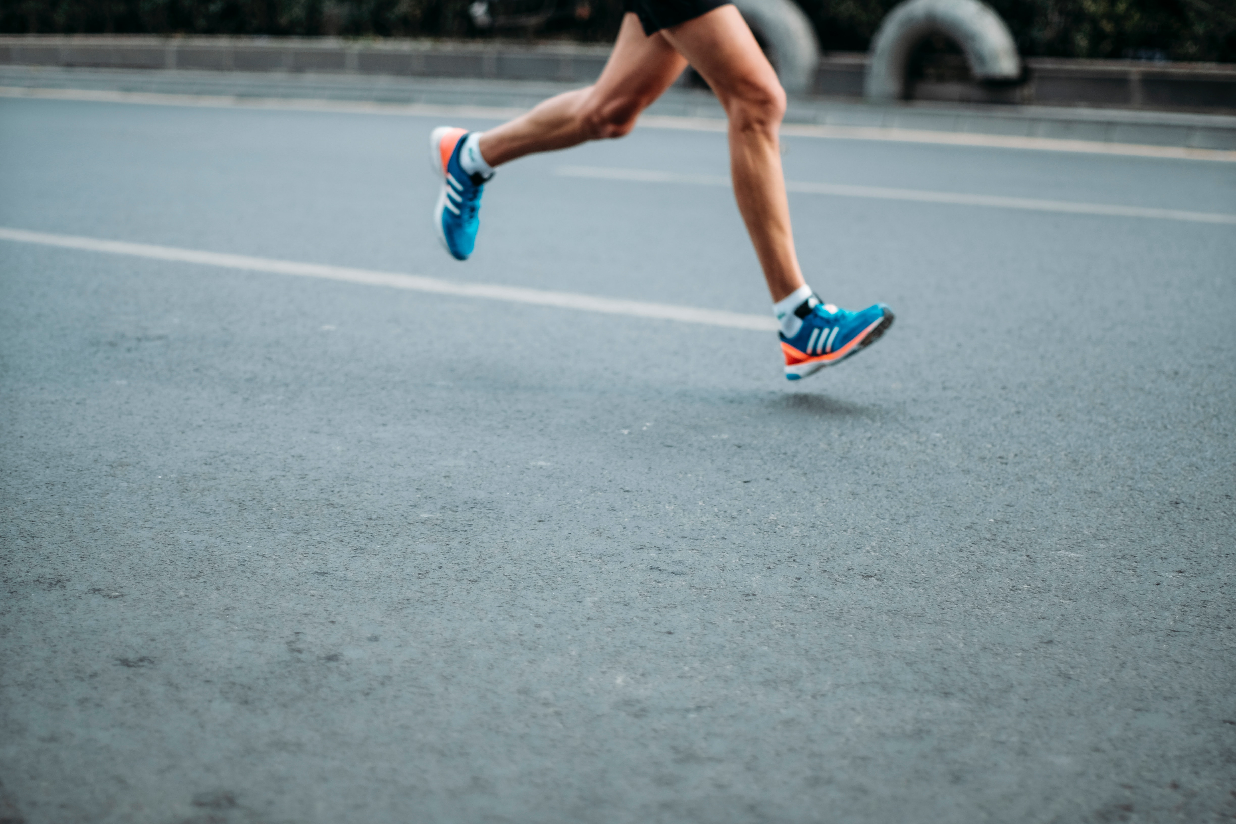 A person's legs wearing a pair of blue-and-white Adidas running shoes running